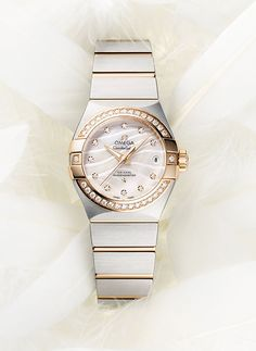 "The Omega Constellation Pluma has a mother-of-pearl dial, in natural white or blue, which features an engraved, wavy pattern that recalls the shapes of a feather (""Pluma"" is Latin for ""feather""). The white-dialed model has a bezel in 18k rose gold and 18k rose gold links in the steel bracelet."
