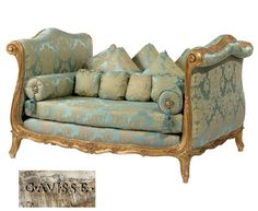 A LOUIS XV GILT WALNUT LIT DU JOUR  STAMPED TWICE G. AVISSE, MID-18TH CENTURY AND RE-GILT  With high arched out-scrolled sides punctuated with floral sprays within a paneled border, the frame covered in aqua, blue and beige silk damask with loose pillows and bolsters, the apron with scalloped edge and with floral sprays, the whole raised on short cabriole legs, regilt, bottom re-supported