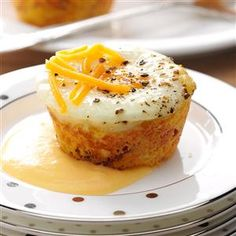 Shirred Egg Corn Muffins Recipe -For our brunches, we bake eggs in cornbread cups. With cheddar sauce and more cheese sprinkled on top, they make a cute little meal-in-one package. —Lisa Speer, Palm Beach, Florida