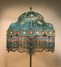 Victorian style lampshade with multicolored beads strung in a particular pattern and embroidery on the top cloth.