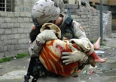 """Soldier comforts a child fatally injured in a car bomb blast."" It's almost incomprehensible to me that my heart can hurt this much when I see the horror we can inflict on one another...especially when that horror claims the lives of the innocent. As much as I want my country back on track, and standing up for those innocent souls - what I earnestly want even more is for Jesus Christ to come back and claim His own. I long for the days when the lions and lambs will lay together."