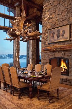Rustic dining room, a luxury lodge In Wyoming..interior design ideas, mountain lodge, cabin, fireplace,large windows, antler chandelier, large table, comfortable chairs