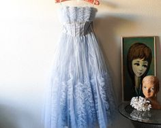 Vintage strapless party or prom dress--no label. Light or powder blue...satin lining...tulle skirt...ruffled tulle accents. Lovely white iridescent sequins in striped design. Side zipper..little skinny belt included. Shows some vintage wear from use along inside top lining, some missing sequins...belt shows the most wear with a bit of yellowing on buckle. *Please note pics* Small in size...though looks like this was taken in along one side about 1/2 to 3/4 of an inch. Frilly and fun...