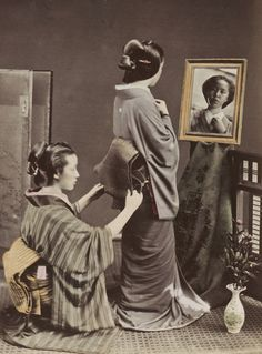 One woman putting an obi on another. Circa 1876, Japan, by photographer Kozaburo Tamamura.