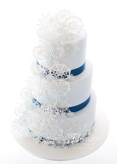 Winter Wonderland wedding cake! Delicate snowflakes floating down a palest of blue cakes with contrasting dark blue ribbon to match in with the decor. The base tier was ginger cake with caramel Italian meringue buttercream and the top tiers were vanilla cake with vanilla bean meringue buttercream.