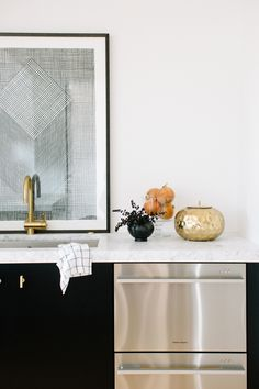 The mix of textures—Carrara marble countertops, brass fixtures—brings warmth to the monochromatic space   archdigest.com