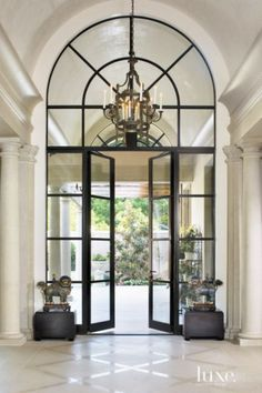 The juxtaposition between late architect Jack Schutts' predilection for modern design and interior designer Joseph Minton's classical aesthetic is beautifully expressed in this Fort Worth home's entry hall, which runs from the front door to the back terrace seen here. Custom steel-framed Hope's windows and doors alongside a barrel-vaulted ceiling, 10-foot-high Doric columns and Lueders limestone flooring laid in a diamond pattern contribute to this notion.