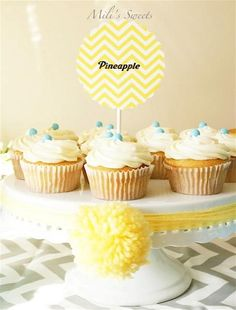 pineapple cupcakes on baby shower table with yarn pom decor by Mili's Sweets