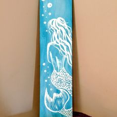 Beautiful hand painted mermaid on carribean blue wood (23x6). Sealed and protected. Perfect addition to your beach decor!!!