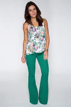 Regata com estampa floral tropical acompanha calça verde flare de linho e salto alto para valorizar a produção.