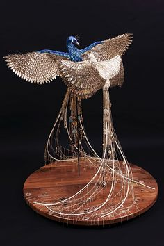 """San Francisco-based artist Laurel Roth builds these Peacock sculptures using many synthetic, shiny, and recycled beauty products that she dubs """"human mating plumage."""" Fake fingernails, barrettes, nail polish, false eyelashes, and jewelry are used, according to Roth, """"to represent the choices involved in biological processes that are unique to humankind."""""""