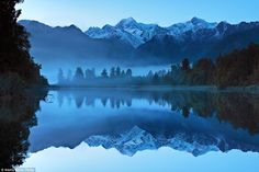 Seeing double: See Mount Tasman and Mount Cook perfectly reflected on the Lake Matheson near Fox Glacier in New Zealand