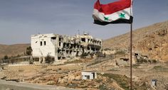 A Syrian flag on the background of ruined houses in the Syrian town of Maaloula, 55 km from Damascus, which was twice captured and looted by Jabhat al-Nusra militants.