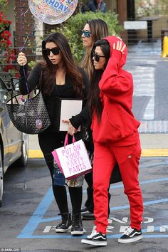Laid-back look: Kourtney donned a bright red Champion tracksuit, complete with hoodie and sweatpants