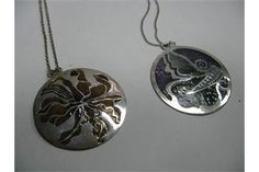 Norman Grant; Two Hallmarked Silver and Enamel Disc Pendant, each on a chain. (2)