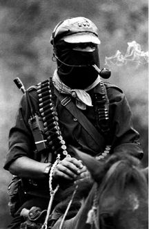 "Commander Marcos of the zapatistas rebel fighters, poet and anarchist. ""Marcos, the quintessential anti-leader, insists that his black mask is a mirror, so that 'Marcos is gay in San Francisco, black in South Africa, an Asian in Europe, a Chicano in San Ysidro, an anarchist in Spain, a Palestinian in Israel, a Mayan Indian in the streets of San Cristobal, a Jew in Germany, a Gypsy in Poland, a Mohawk in Quebec, a pacifist in Bosnia, a single woman on the Metro at 10 p.m., a peasant without…"