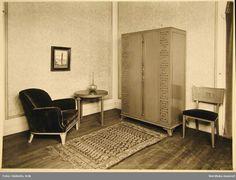 """Axel Einar Hjort. Möbelutställning på Nordiska Kompaniet 1932. Fåtölj, bord, skåp och stol i modellen """"Åbo"""" formgiven av Axel Einar Hjort. @ DigitaltMuseum.se"""