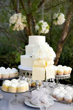 Tiered cake as centerpiece/focal point with cupcakes on various heights below. Like the white and crystal pedestals.