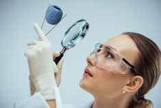 Scientist Looking at a Strawberry With a Magnifying Glass in a Lab Magnifying Glass, Drop Earrings, Health, Lab, Strawberry, Socks, Health Care, Drop Earring, Labs