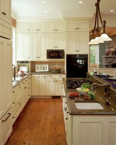 A galley style kitchen that incoprorates lot's of muted beige tones and tropic brown granite countertops.