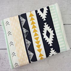 Have you heard? Southwest inspired prints is the absolute hottest trend to hit the nursery bedding world since chevron. Keep baby warm in this trendy gold, navy and mint print blanket! Coordinates wit