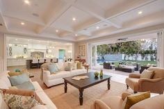 A grand room with folding doors that open up to the manicured backyard with a casual patio. Instead of cathedral ceilings, this great room has beautiful coffered ceilings.