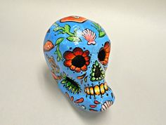 This is a one of a kind hand painted paper mache skull. Inspired by the monsters of the deep this skull grabs attention with its giant squid design.