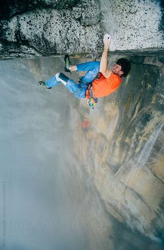 Rock climber/mountaineer climbing an extreme overhanging roof on table mountain by Micky Wiswedel