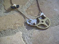 Ce collier est composé d'engrenages d'horloge antique, d'un noeud en cuir et d'une perle de culture portés sur une chaînette couleur bronze. Les pièces métalliques sont patinées pour un effet...