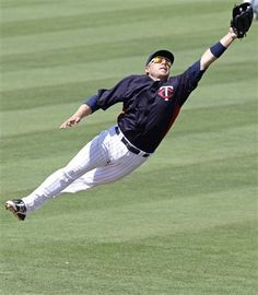 Minnesota Twins second baseman Luke Hughes leaps but can't get a glove on an RBI single by Tampa Bay Rays' Jeff Salazar during the sixth inning of a spring training baseball game in Fort Myers, Fla