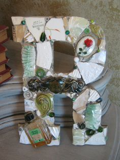 Mosaic letter R with rose, vintage bottle and Victorian hardware in green and cream, mosaic art.