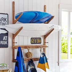Surf Rack System // A cool and convenient place for your gear, this surf rack blends coastal inspiration with smart organization. Two shelves house your surfboards and pegs keep your other surf stuff in place.