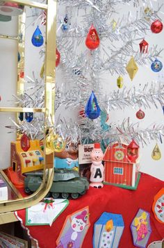 Vintage Fisher Price toys under a silver tinsel Christmas tree with a DIY felt tree skirt.