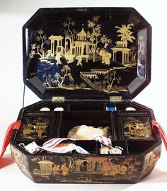 The interior of the box has spaces for sewing equipment. The tray lifts out to reveal a large undivided section. The two decorated lids lift out.
