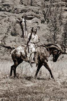 Mounted Warrior - Native American Indian in traditional costume against rock cliffs in western Wyoming. © Mike R. Jackson
