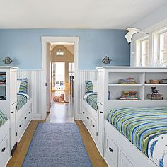 Two rows of built-in beds with drawers underneath and bookshelves in place of headboards make the most of the long, narrow space in this Maine cottage children's sleep space.