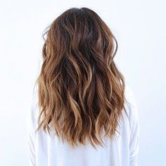Medium hair style, brown hair color with highlights, wavy brown hair