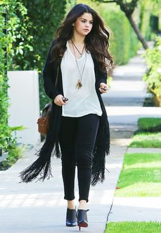 Selena Gomez wears a white t-shirt, fringe black cardigan, shoulder bag, layered necklaces, and heeled ankle booties