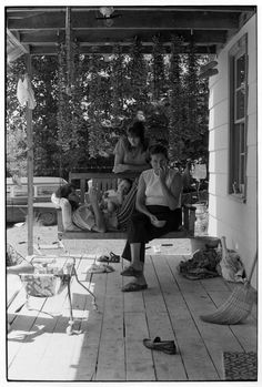 Women sitting on a porch swing, strung green beans hanging above him.. From Duke Digital Collections. Collection: William Gedney Photographs and Writings.