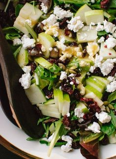 Fresh green salad recipe featuring sliced apple, toasted pepitas, dried cranberries and crumbled goat cheese. Apple cider vinaigrette recipe included.