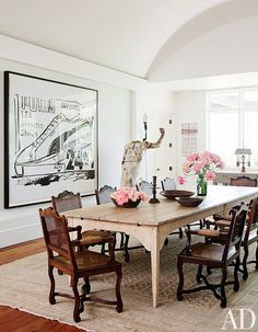 Rustic dining space with many pink flowers, black and white art, and sculpture