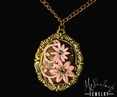 Antiqued brass pendant put on a copper chain (no clasp). On the metal base is polymer clay hand shaped into flowers and leaves with Swarovsky crystal embelishments.The necklace has a very modern look,really fun to wear and attracts a lot of attention with the crystal sparkles.