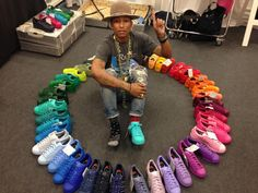 Super-talented Pharrell Williams surrounded by colourful Adidas shoes.