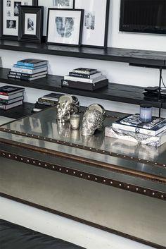 Detaljebillede fra stuen, hvor et mix af kunst, bøger og nips er kunstfærdigt arrangeret på hylder og en gammel metalkuffert.