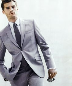 He's tall, dressed in a fine gray suit, white shirt, and black tie. #christiangrey #jamiedornan