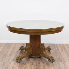 This round dining table is featured in a solid wood with a glossy oak finish. This dining table has some cosmetic wear but is otherwise in good condition with a round glass table top, pedestal base and intricate carved claw feet. Perfect for formal or causal dining! #traditional #tables #diningtable #sandiegovintage #vintagefurniture
