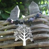 """This necklaces features a tree pendant on a beautiful mix of amethyst and black jasper stone chips. It also has midnight stone chips (deep purple with sparkles). It is approx. 23"""" long before the pendant."""