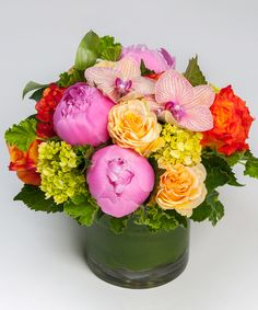 Peony Sunrise A bright and beautiful spring collection of peonies and roses with an orchid accent is designed in our signature leaf-lined cylinder vase. Mother's Day flowers