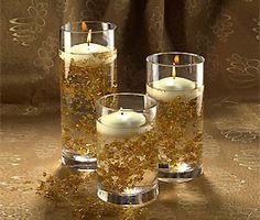 "submerging our flexible garland of sparkling gold beads and topping it with ivory floating candles. Cylinder Vases and Gold Garland Set includes: 1 each Large, Medium and Small Cylinder Vases, 3 Gold Bead Garlands and 3 Ivory 3"" Floating Candles"
