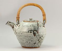 William Marshall (British, 1923-2007), A Teapot, stoneware, mottled cream layered over iron glazes, the rounded body mounted with a loop handle and short spout, impressed WM and Leach Pottery seals